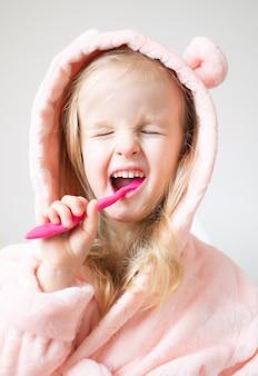 Gelukkig meisje haar tanden, roze tandenborstel, tandhygiëne, ochtendnacht gezonde concept levensstijl borstelen