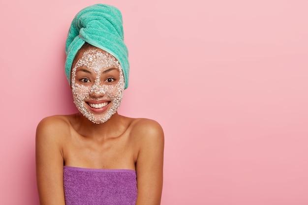 Gelukkig meisje heeft blije uitdrukking, staat in de badkamer na het nemen van een bad, draagt peeling scrub rond gezicht, gewikkeld in zachte handdoeken