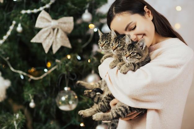 Gelukkig meisje houden en knuffelen drie schattige kittens