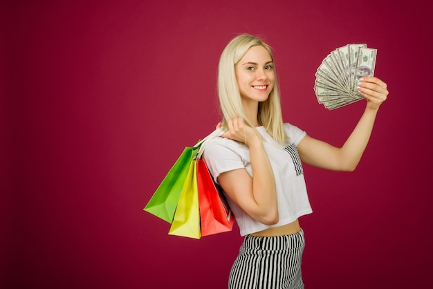Gelukkig meisje houdt honderd dollarbiljetten en boodschappentassen op robijn