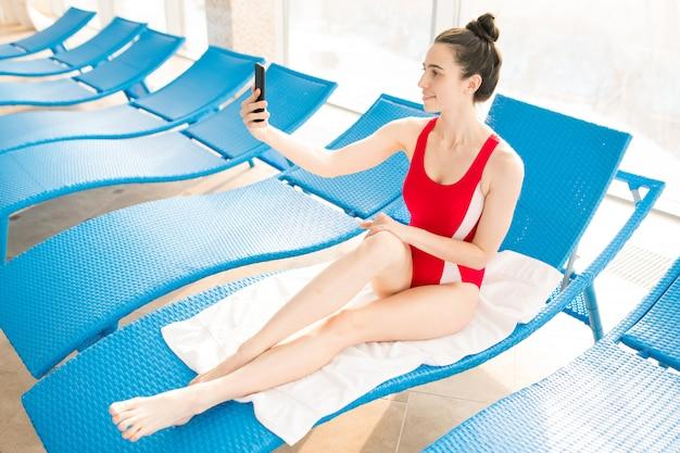 Gelukkig meisje in badmode selfie maken zittend op ligstoel door raam na het zwemmen opleiding