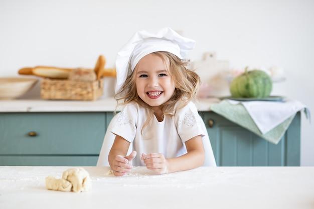 Gelukkig meisje in chef-kokhoed in keuken