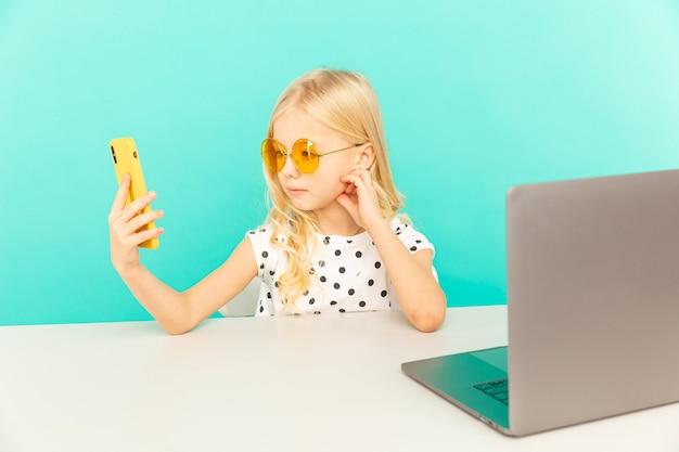 Gelukkig meisje in de blauwe studio die voor camera voor vlog spreekt. werken als blogger, video-tutorials opnemen voor internet.