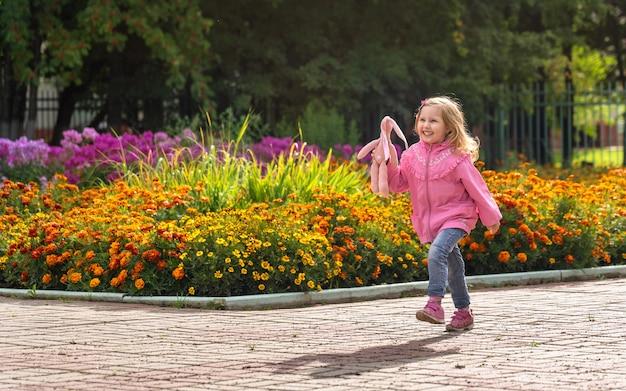Gelukkig meisje in denim broek en een lichte jas en sportschoenen loopt door het park