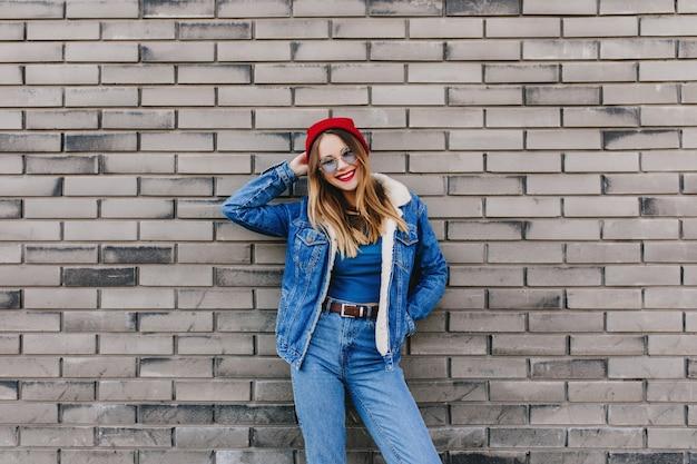 Gelukkig meisje in denimuitrusting die zich voor bakstenen muur bevindt. buiten foto van kaukasische jonge dame draagt jeans en rode hoed positieve emoties te uiten.