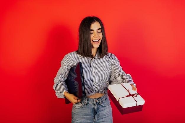 Gelukkig meisje in een blauw shirt en spijkerbroek staande op een rood oppervlak en strekt zich uit rood-witte doos met cadeau.