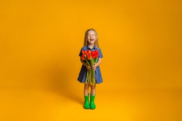 Gelukkig meisje in een blauwe denimjurk en groene rubberen laarzen met rode tulpen op een gele muur