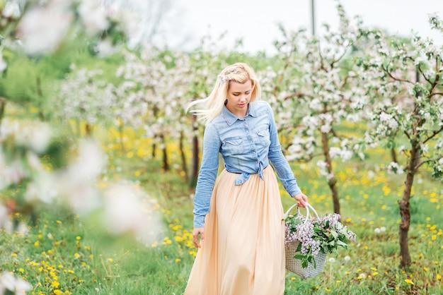 Gelukkig meisje in een bloeiende tuin. blonde jonge vrouw in in het voorjaar bloeiende tuin,