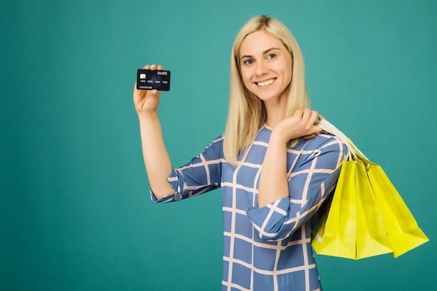 Gelukkig meisje in een geruite blouse houdt creditcard en boodschappentassen op blauw