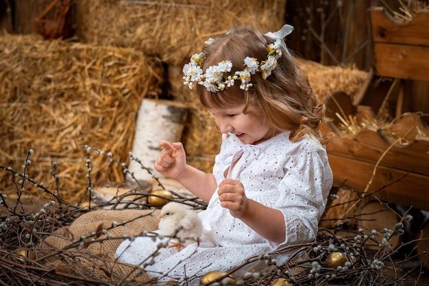 Gelukkig meisje in een jurk en een krans zit in een nest met schattige chick