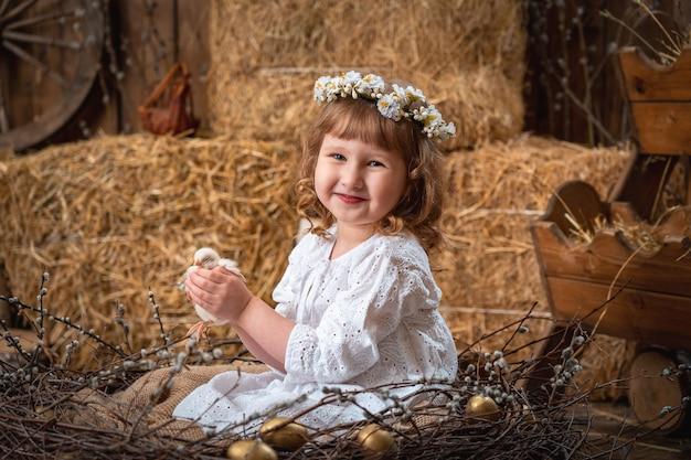 Gelukkig meisje in een jurk en krans zit in een nest en houdt een schattige kip.
