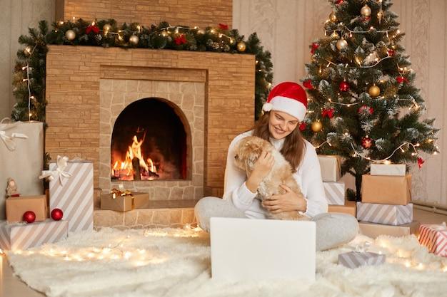 Gelukkig meisje in een rode hoed met video-oproep op laptop en zittend met schattige hond op kerstboom met verlichting en cadeautjes in feestelijke kamer, op zoek glimlachend ar apparaatscherm.