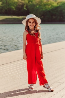 Gelukkig meisje in een rode jumpsuit en witte hoed aan de waterkant genieten van de natuurvrijheid