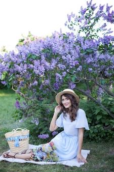 Gelukkig meisje in een strohoed zit op een picknick in de zomerweekends in de lila tuin in de open lucht