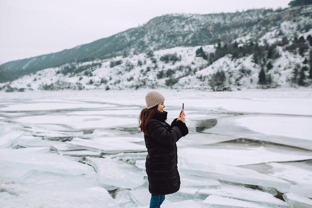 Gelukkig meisje in een winterjas staat tegen de achtergrond van een bevroren rivier en neemt de foto bij een prachtig landschap.