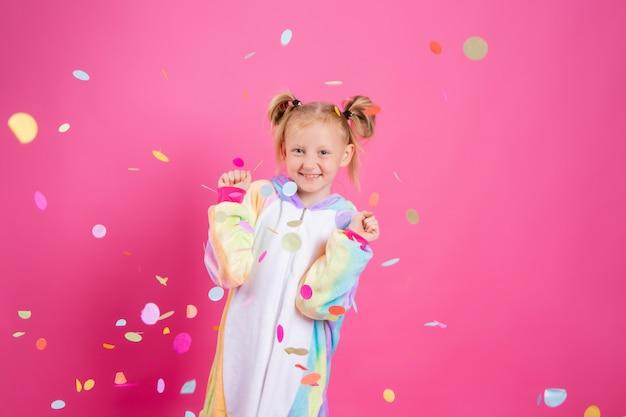 Gelukkig meisje in eenhoorn kigurumi op een roze muur verheugt zich in multi-coloured confetti