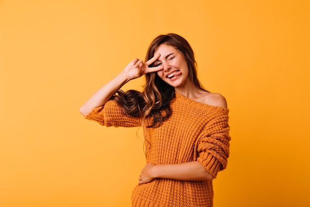 Gelukkig meisje in gebreide trui poseren met tong uit. studio portret van goedgehumeurde donkerharige dame die grappige gezichten maakt.