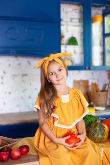 Gelukkig meisje in gele jurk in herfst decor met pompoenen in keuken, halloween vakantie. oogsten. gezonde voeding, vegetarisme, vitamines, groenten.