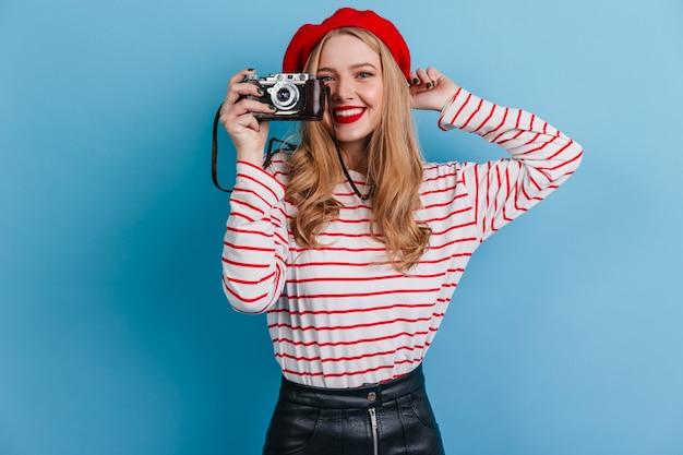 Gelukkig meisje in gestreepte shirt met camera. frans vrouwelijk model dat foto's op blauwe muur neemt.