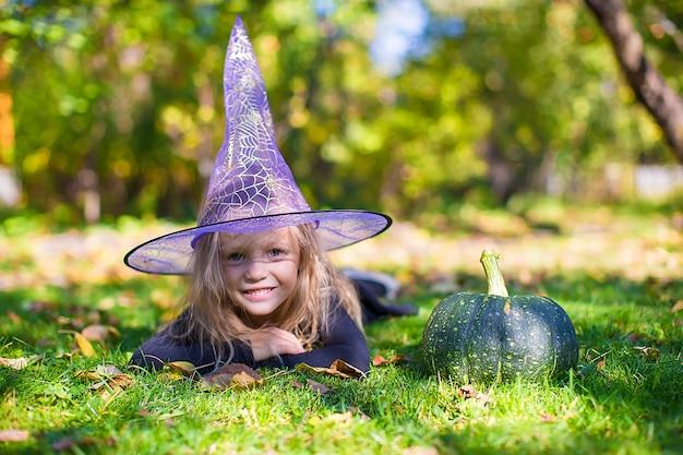 Gelukkig meisje in halloween-kostuum met hefboompompoen. brug of traktatie