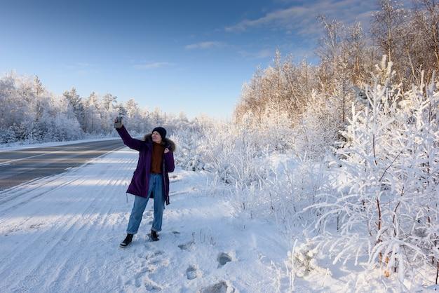 Gelukkig meisje in het winterbos neemt een selfie in de buurt van de boom bedekt met sneeuw.