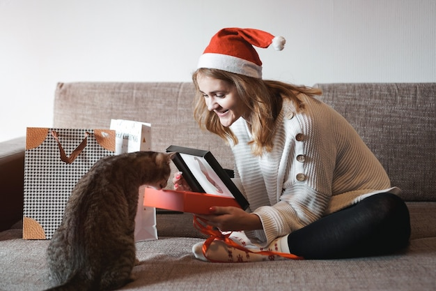Gelukkig meisje in kerstmuts kerst geschenkdoos openen en spelen met kat.