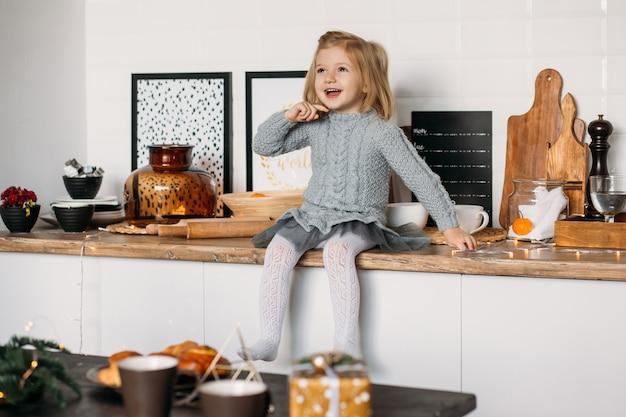 Gelukkig meisje in keuken thuis.