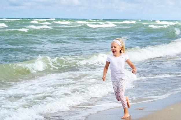 Gelukkig meisje in kleren op het strand van de baltische zee aan het koerse land in litouwen.