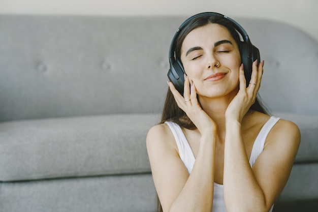 Gelukkig meisje in koptelefoon luistert naar muziek thuis