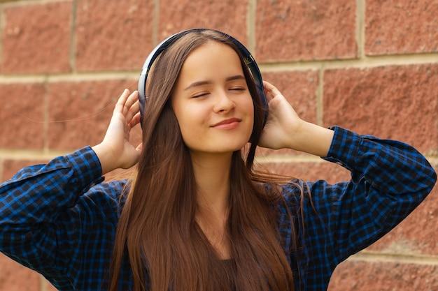 Gelukkig meisje in koptelefoon op straat luisteren naar muziek aan de telefoon, zingen, dansen, glimlachen