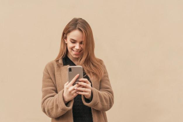 Gelukkig meisje in modieuze kleren, die een laag dragen, smartphone op een beige achtergrond gebruiken, het scherm bekijken en glimlachen