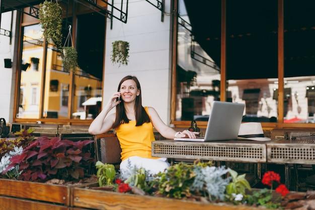 Gelukkig meisje in openlucht straatcafé zittend aan tafel met laptop pc-computer, praten op mobiele telefoon, aangenaam gesprek voeren, in restaurant tijdens vrije tijd