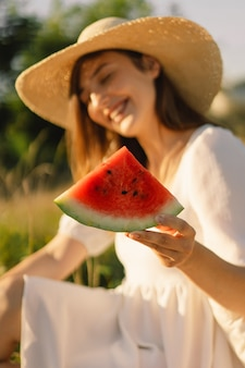 Gelukkig meisje in openluchtpark met verfrissende watermeloen fruitvrouw eet een stuk watermeloen