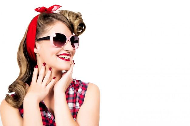 Gelukkig meisje in pin-up stijl die zonnebril op witte achtergrond draagt