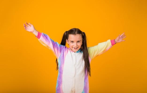 Gelukkig meisje in pluche pyjama geniet op een gele achtergrond met een plek voor tekst