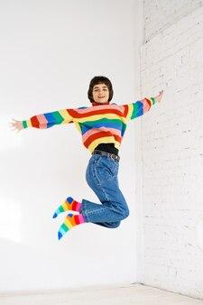 Gelukkig meisje in regenboogtrui springt op lichte achtergrond kaukasische jonge vrouw springen met geluk...