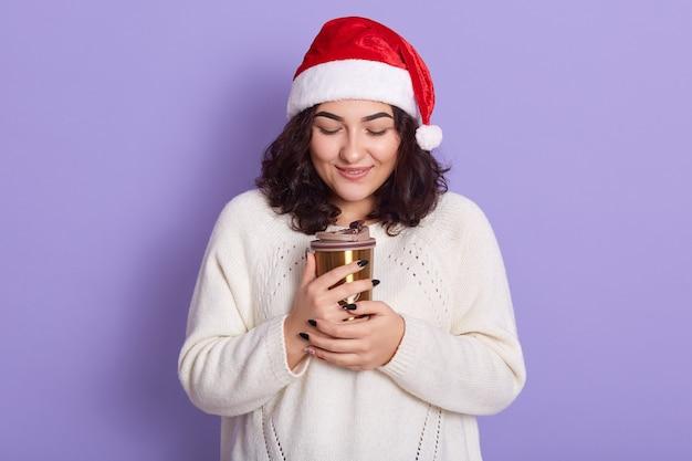 Gelukkig meisje in rode kerstmuts en witte gebreide truien, houdt thermomok thee of koffie, poseren geïsoleerd op lila muur muur, dame zonnebaden handen in koude dag.