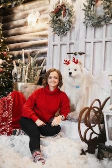 Gelukkig meisje in rode nieuwjaarstrui en scandinavische sokken zit op de trap en poseren met schattige sneeuwwitte samojeed-hond bij kerstinterieur. concept van nieuwjaarsfeest en decoraties