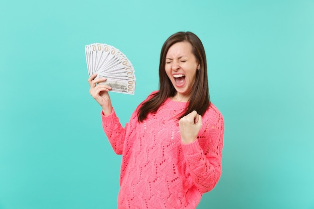 Gelukkig meisje in roze trui met gesloten ogen schreeuwend, houdt veel dollars bankbiljetten, contant geld, winnaar gebaar geïsoleerd op blauwe achtergrond. mensen levensstijl concept. bespotten kopie ruimte.