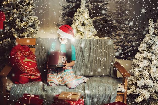 Gelukkig meisje in santa claus-hoed met heden op laag.