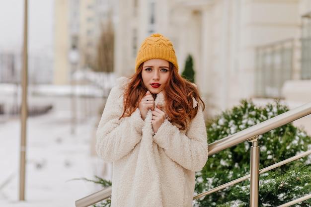 Gelukkig meisje in schattige gele hoed genieten van de winter. geïnteresseerde dame die de dag van december buiten doorbrengt.