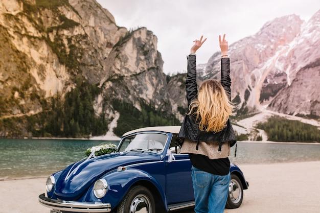 Gelukkig meisje in stijlvolle kleding met plezier in italië kijken naar bergen en grappig dansen met handen omhoog