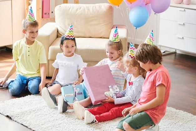Gelukkig meisje in verjaardag glb grote geschenkdoos uitpakken zittend op de vloer onder haar vrienden thuis partij