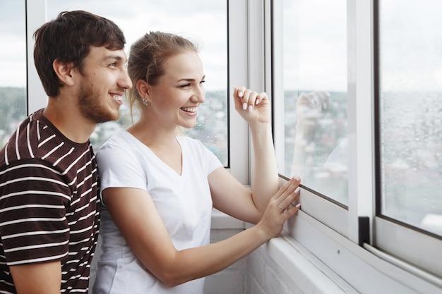 Gelukkig meisje in wit t-shirt en man met een baard, leuk paar kijkt uit het raam in hun nieuwe huis