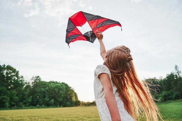Gelukkig meisje in witte kleren veel plezier met vlieger in het veld. prachtige natuur.