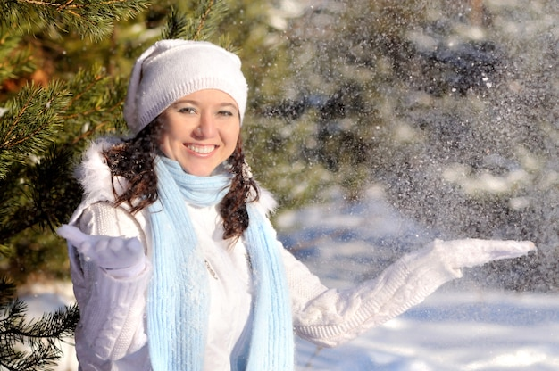 Gelukkig meisje in witte winterkleren, muts, handschoenen en blauwe gebreide sjaal, werpt sneeuw en camera kijken