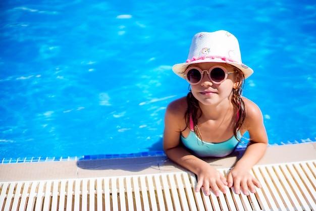 Gelukkig meisje in zonnebril en hoed in buitenzwembad van lux