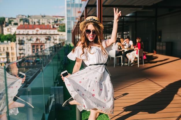 Gelukkig meisje in zonnebril luistert naar muziek via een koptelefoon op het terras. ze draagt een witte jurk met blote schouders, rode lippenstift en hoed. ze is aan het dansen.