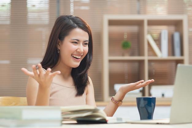Gelukkig meisje kijk naar laptopscherm luister en leer online cursussen in appartement met videogesprek, jonge ondernemer aziatische zakenvrouw die thuis werkt met internet met behulp van computer