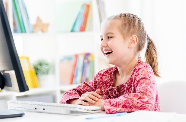 Gelukkig meisje kijken naar computerscherm zittend aan een bureau in de klas